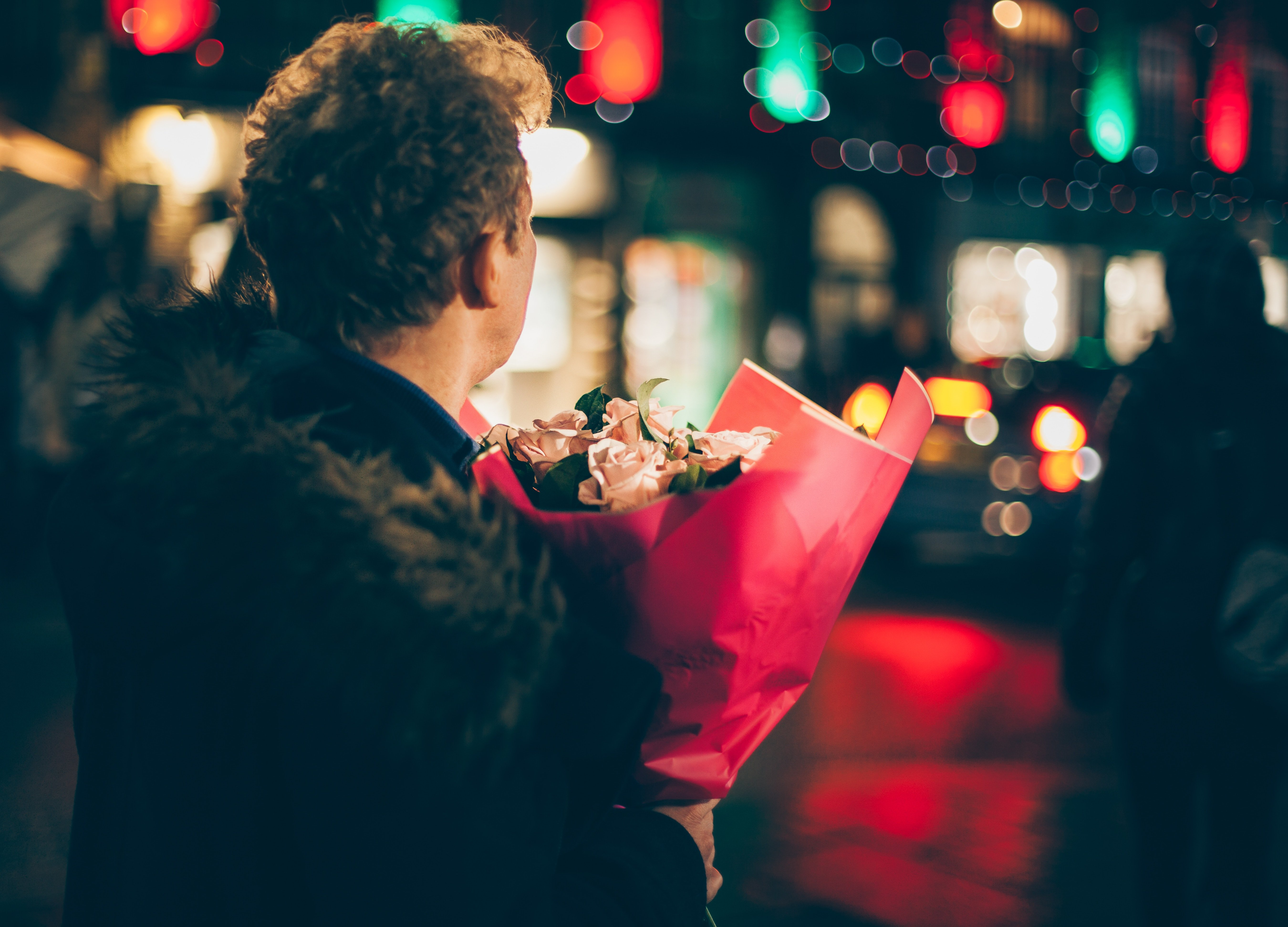 man waits at a bright lit up intersection carrying a bouquet of flowers